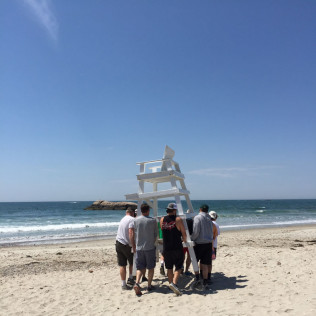 Guys carrying lifeguard stands